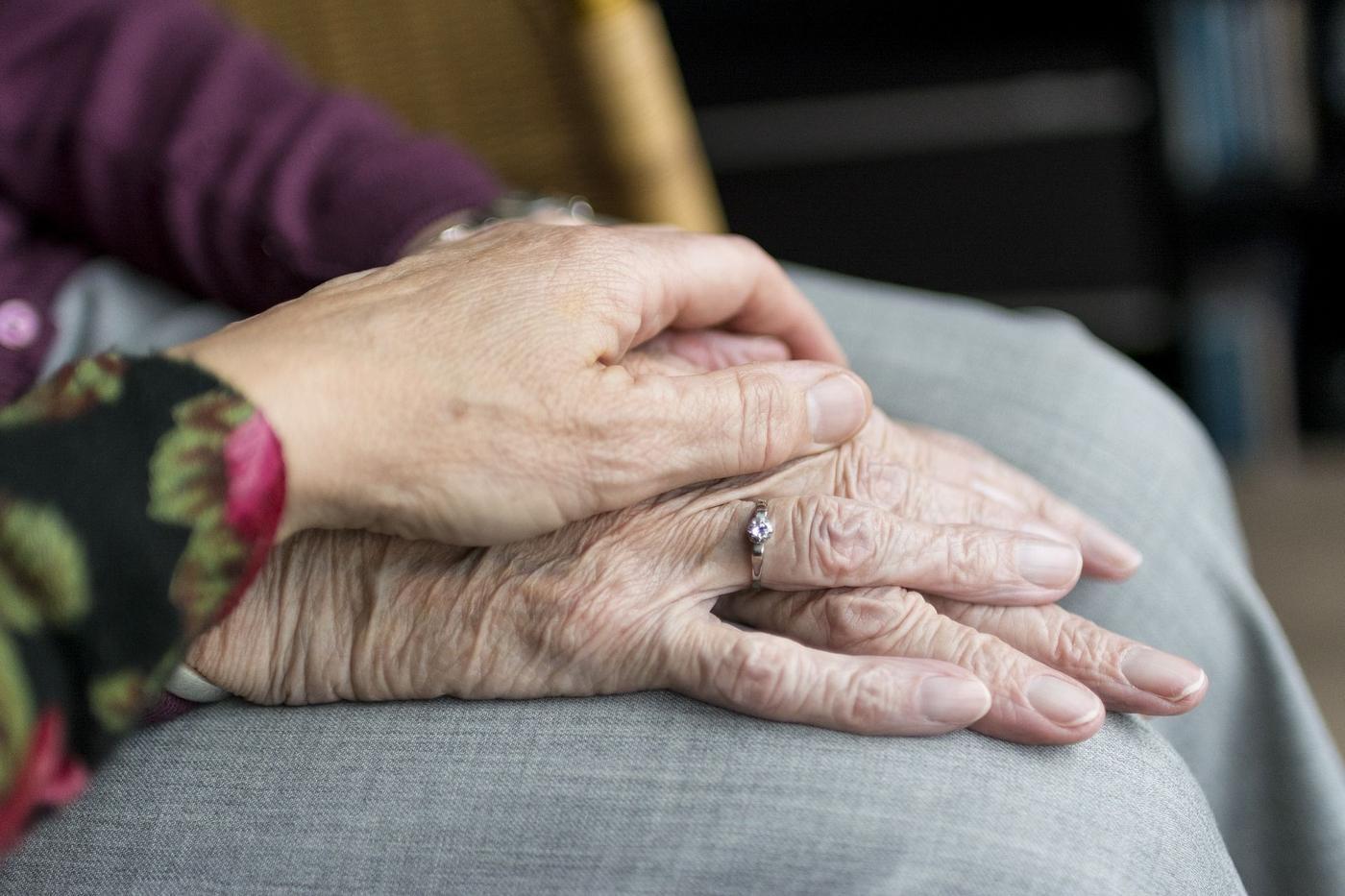 Ett par äldre händer, en yngre hand ovanpå