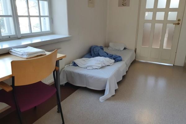En obäddad madrass på ett golv.