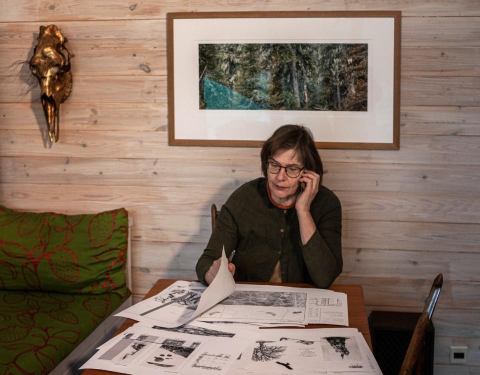 Kvinna sitter vid ett bord och ser på bilder.