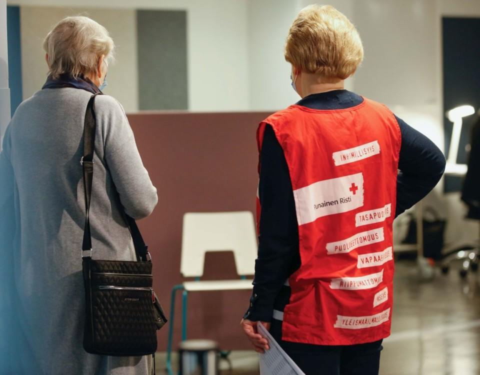 Frivillig från Röda Korset handleder kvinna