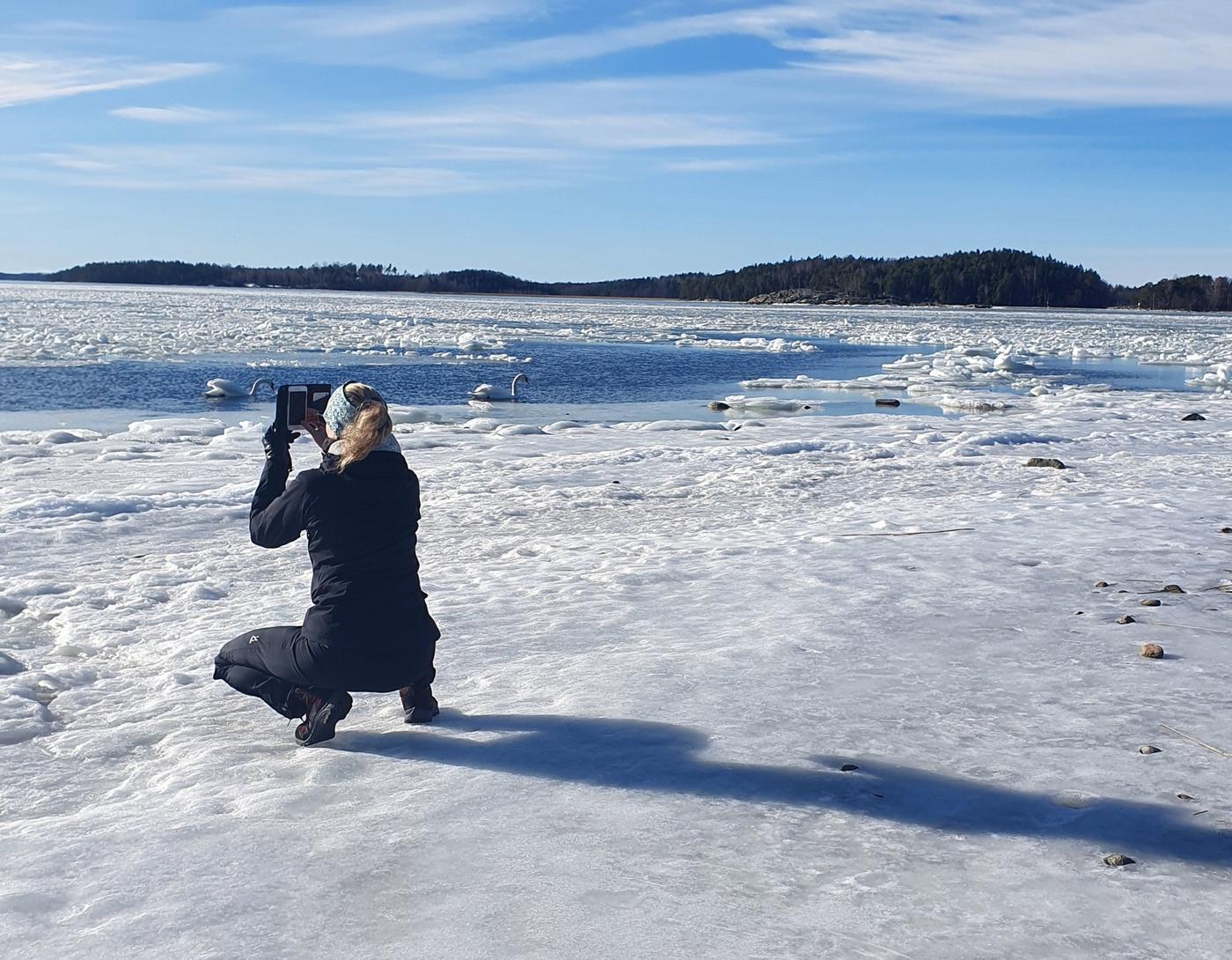 Kvinna på huk vid is.