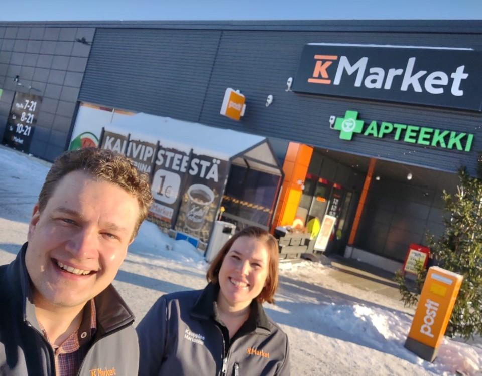 Två glada köpmän framför en butik.