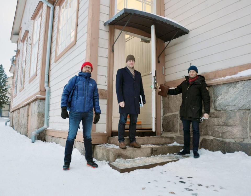 Tre män står vid skoltrappa