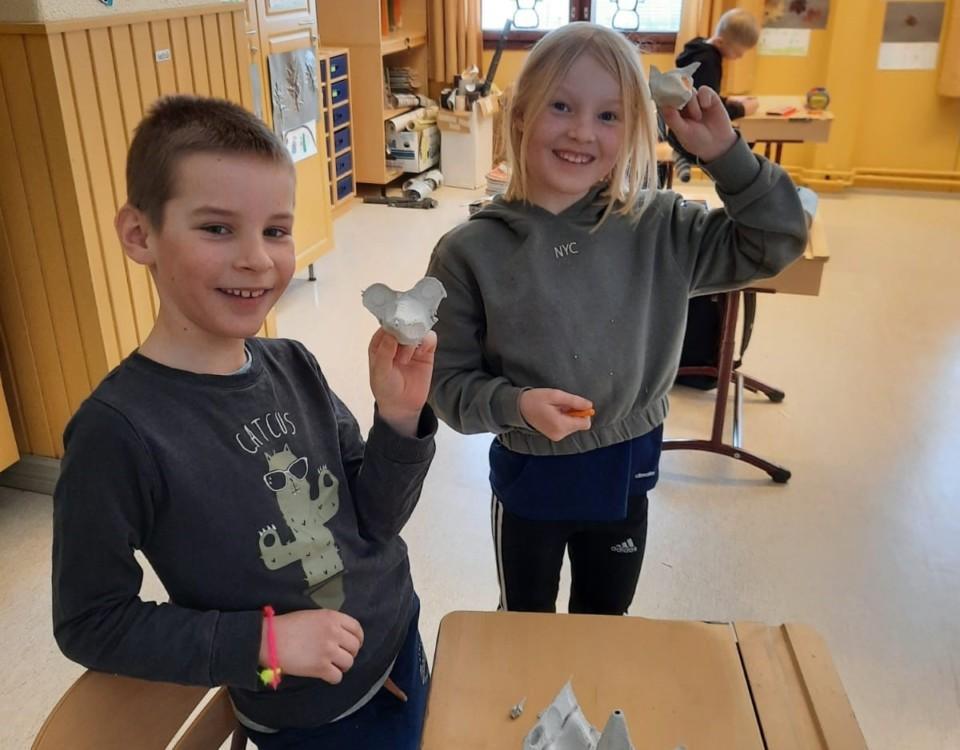 En flicka och en pojke visar upp små handdockor i kartong