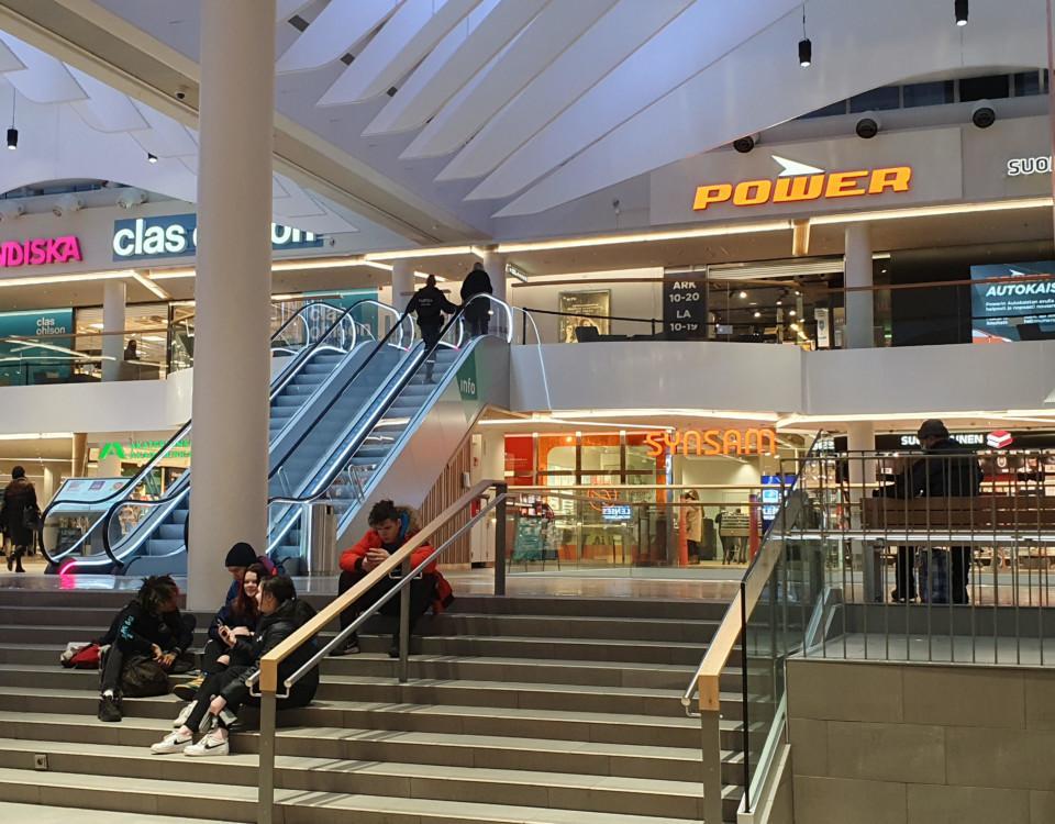 Unga personer sitter på trappan i ett köpcentrum.