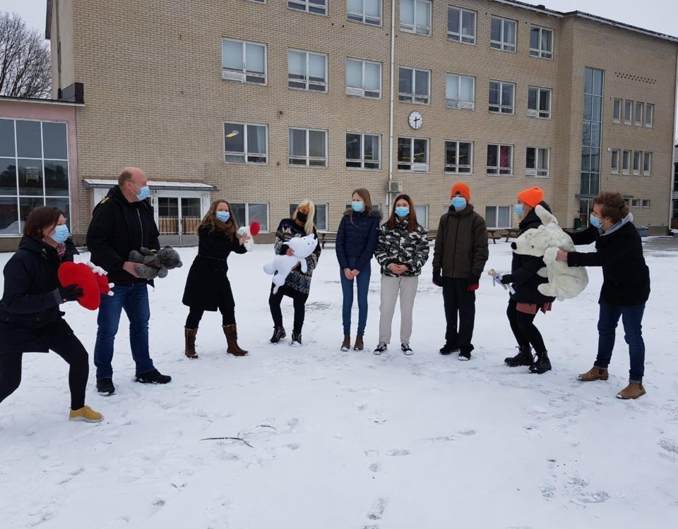Vuxna kring några ungdomar på en vintrig skolgård, kampanjstart