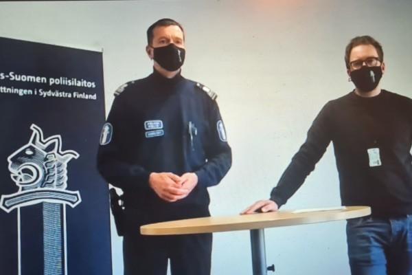 två män i munskydd bakom ett bord