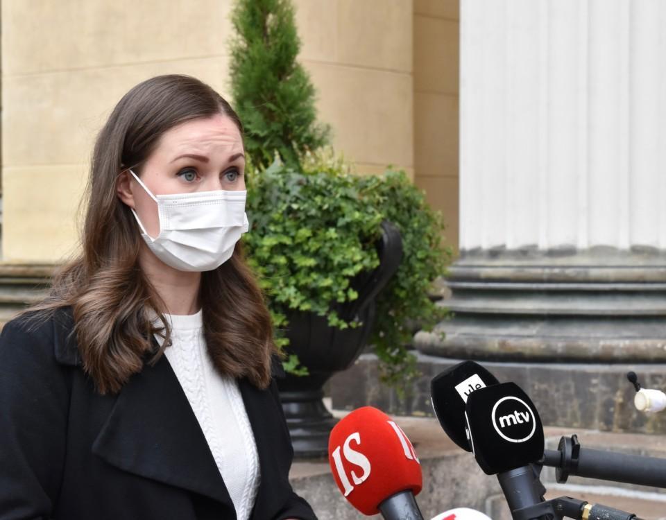 Kvinna med munskydd och mikrofoner bakom sig.