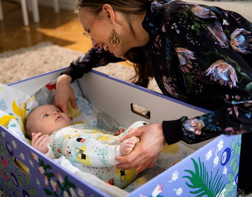 En kvinna som lägger ner en baby i en fodrad låda.