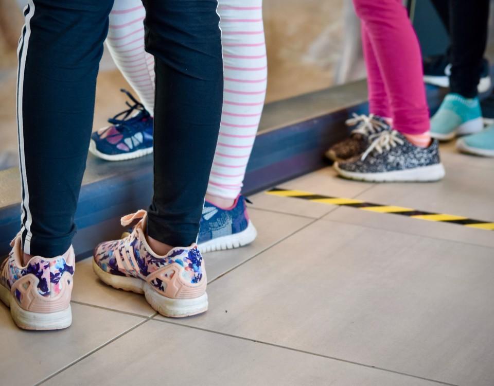 barnfötter och en tejpad linje på ett golv
