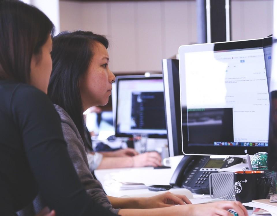 två kvinnor sitter framför en datorskärm