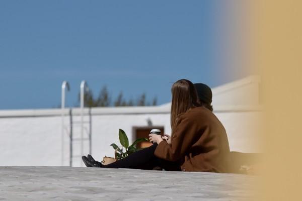 två ungdomar sitter och samtalar kring en kopp kaffe