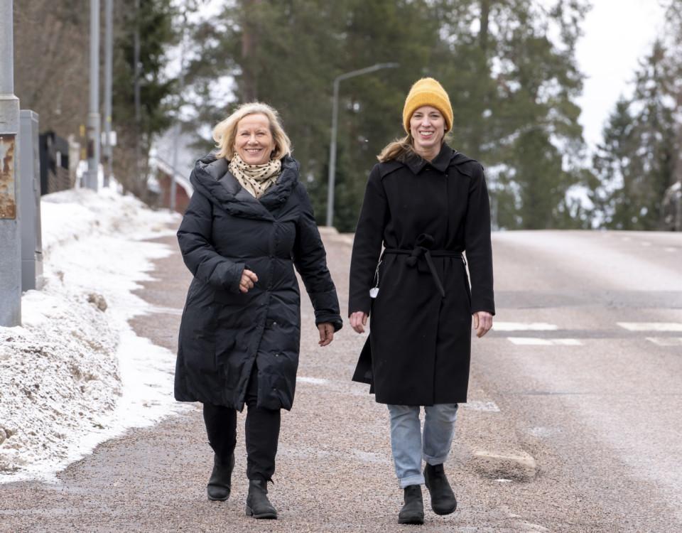 två damer promenerar längs med gata