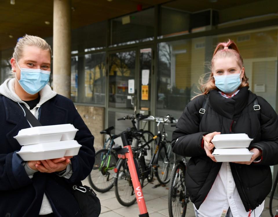 två kvinnor med munskydd står med hämtmatslådor i sina händer