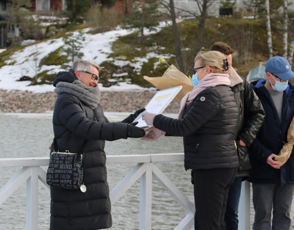 kvinna tar emot pris o tavla, står utomhus