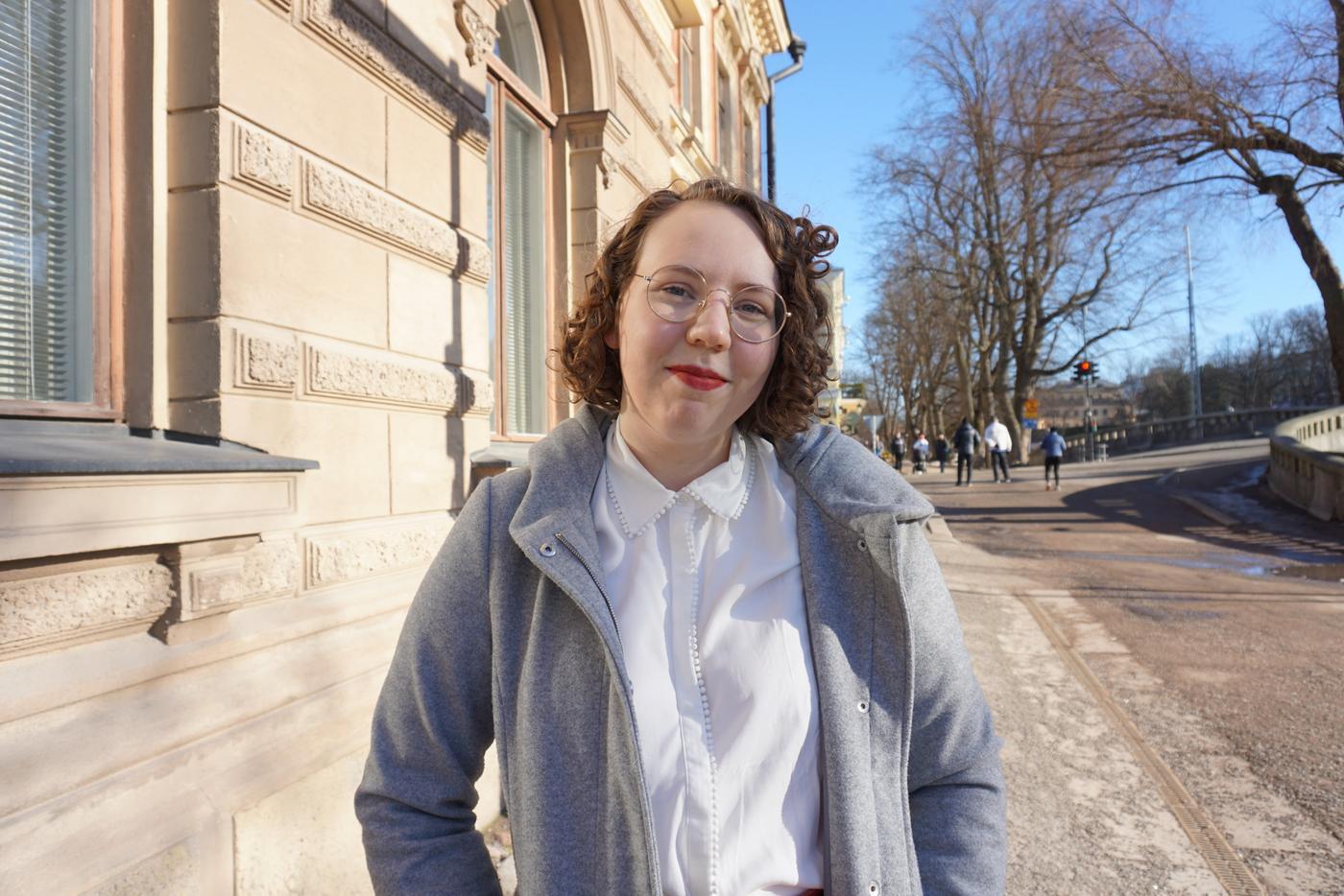 en leende kvinna i runda glasögon står med händerna i fickorna på en vårjacka