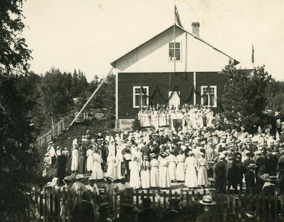 en gammal svartvit bild på ett hus och en mängd festklädda människor på gården