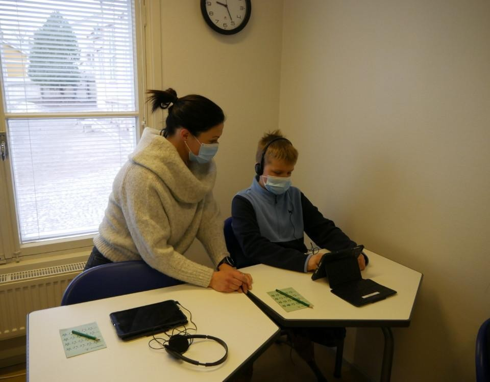 En pojke sitter med hörlurar och tittar på en skärm medan en kvinna sitter bredvid. Båda bär munskydd.