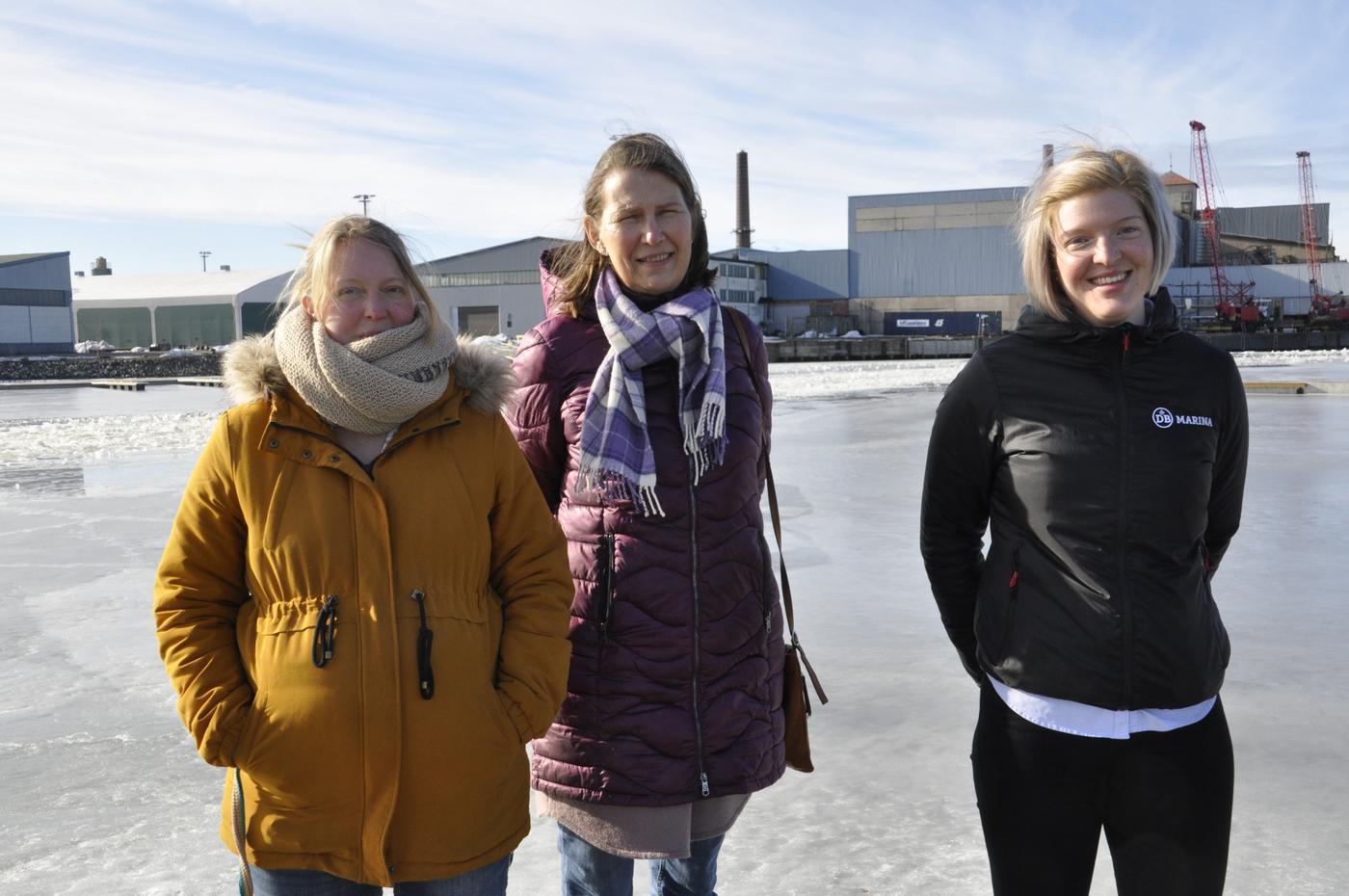 Tre damer vid en hamn