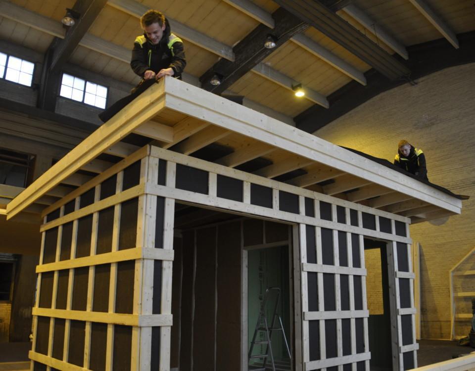 Ett modulhus under arbete i en hall. PÅ taket två unga arbetande män