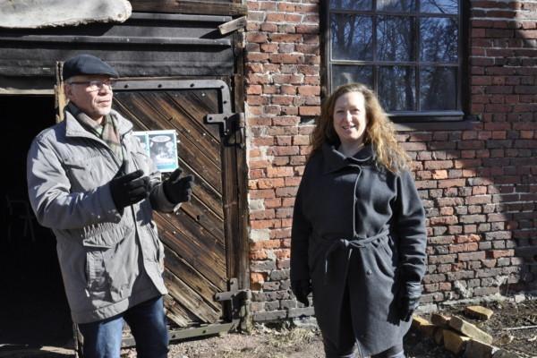 Två personer diskuterar framför en gammal byggnad