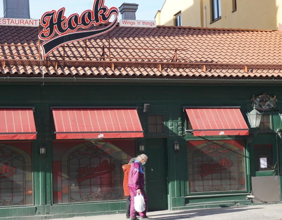 två äldre personer med munskydd går förbi en stängd restaurang