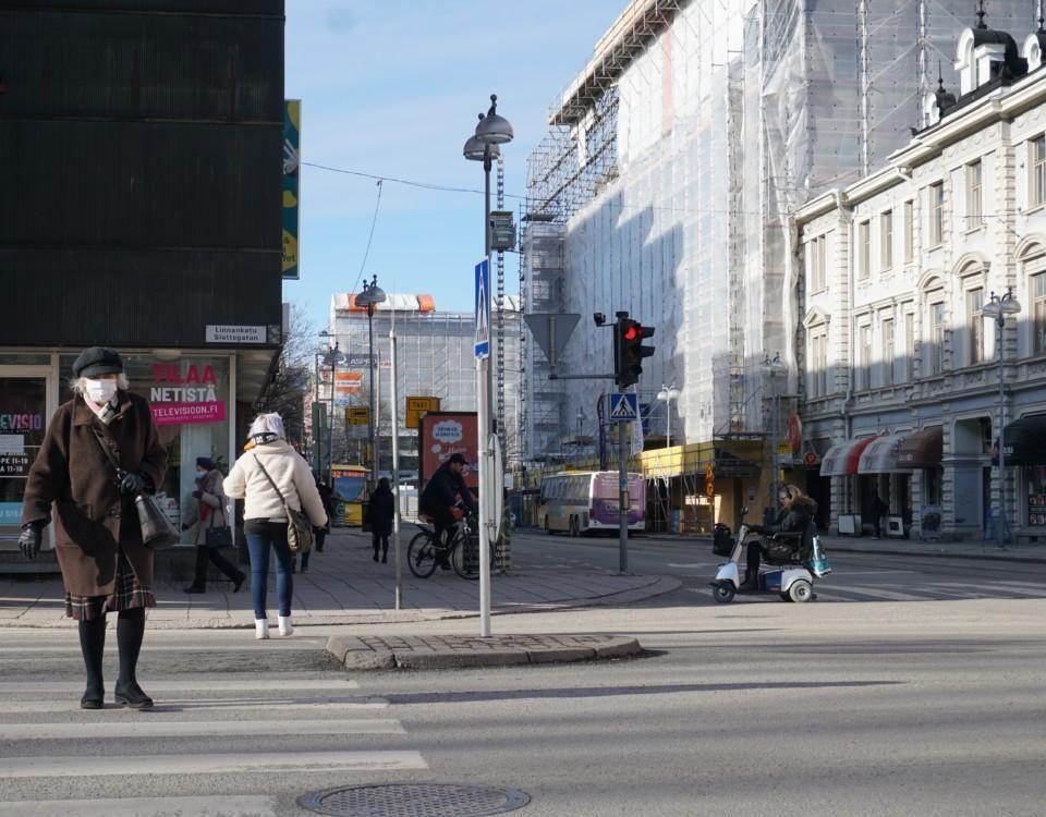 en kvinna med munskydd korsar en gata