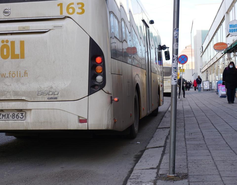 bakändan av en buss, i bakgrunden går en person med munskydd