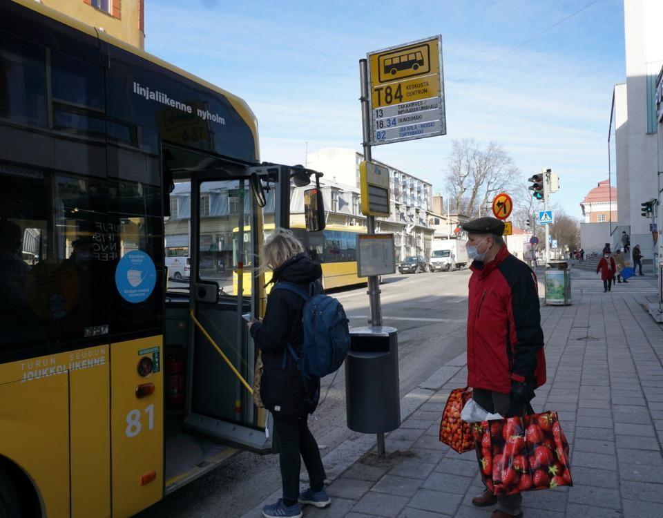två personer med munskydd stiger på en buss