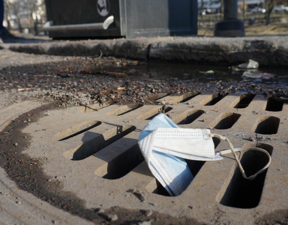 ett munskydd ligger i en gatubrunn