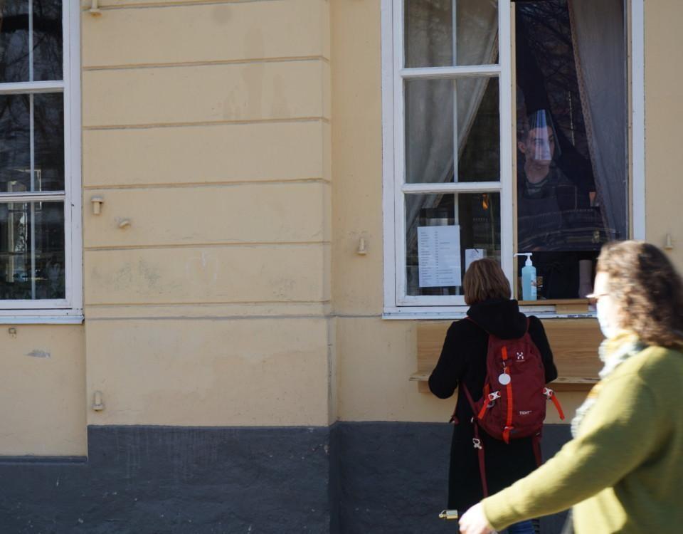 en person beställer en kaffe genom ett fönster