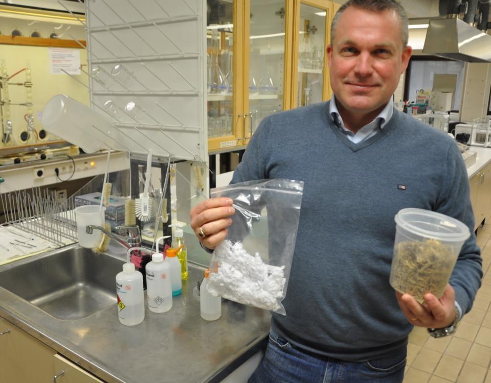 man i laboratorium håller upp en påse med textilfiber tillverkade av halmstrån gjorda visar upp biomassa och