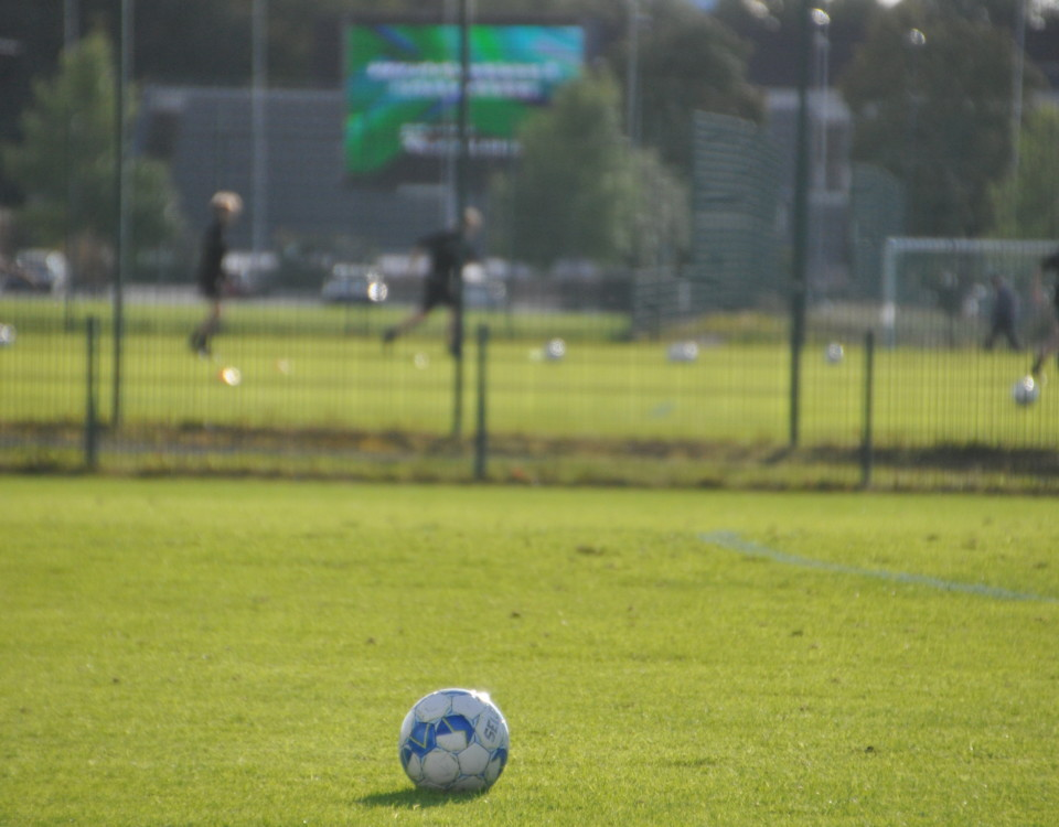 en fotboll ligger på fotbollsplan, i bakgrunden skymtar flera fotbollsspelare
