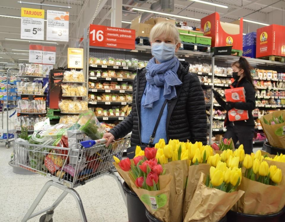 En kvinna med en butikskärra i en mataffär.