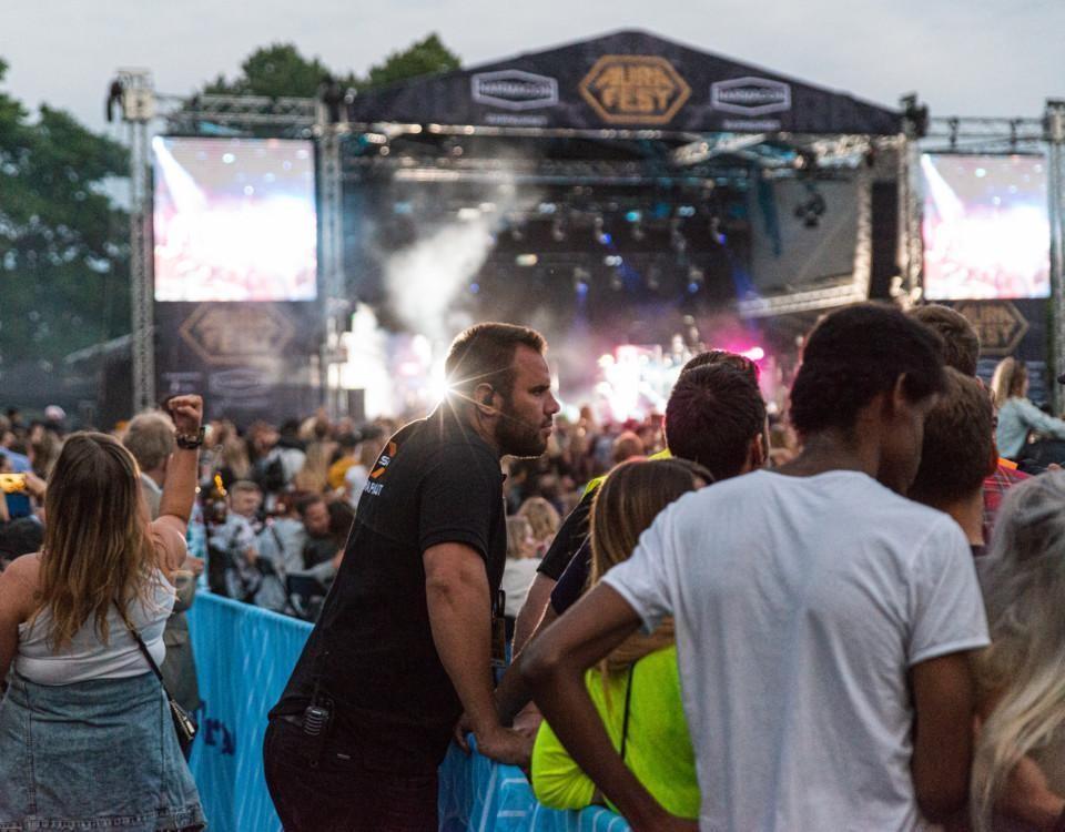 ordningsvakt lutar sig över barriär på musikfestival