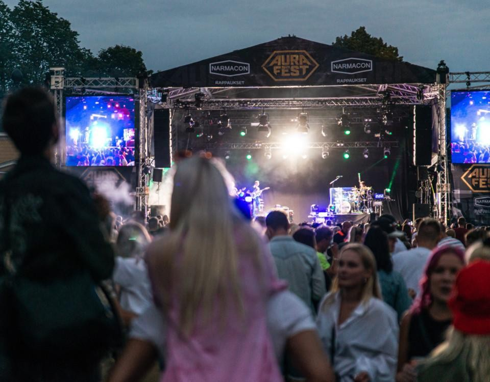 publik i kvällens mörker framför scen i park