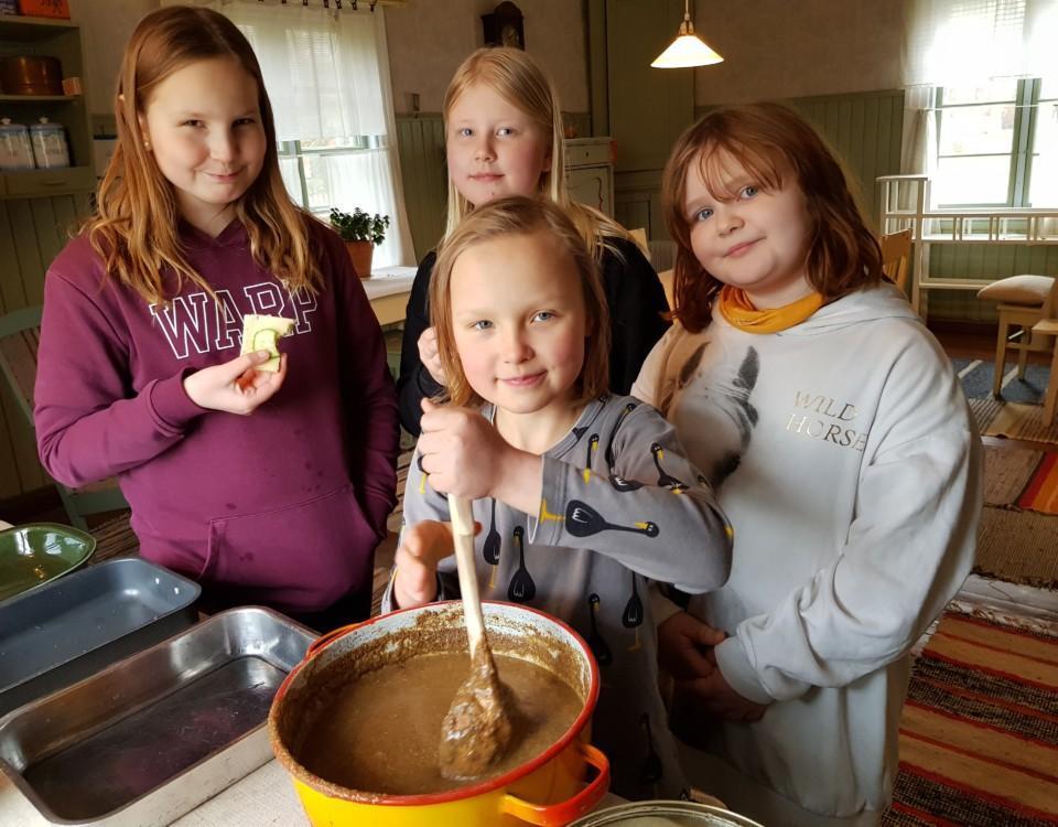 Fyra barn i skolåldern vid en kastrull med memmasmet