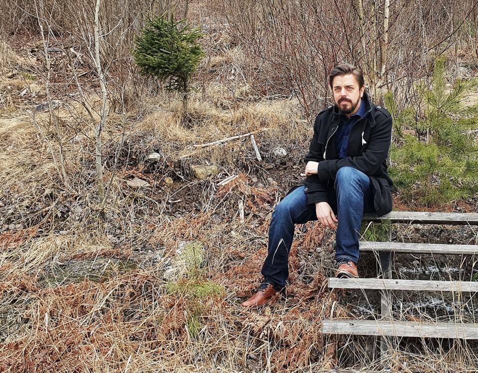 Anders Helenius sitter på en gammal trätrappa mitt i naturen.