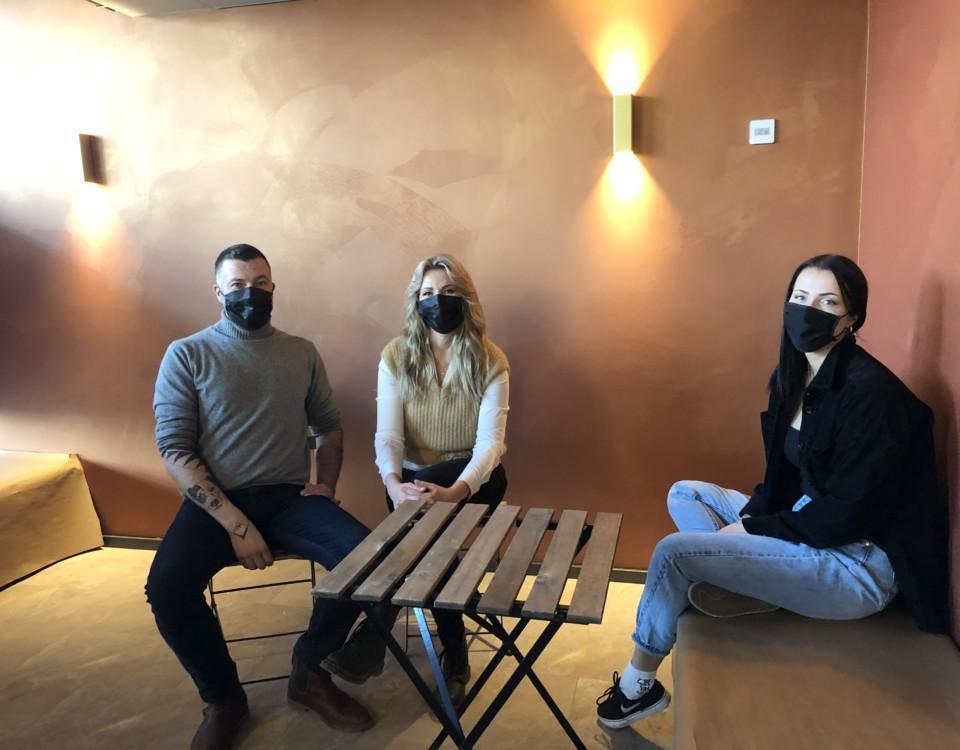 en man och två kvinnor med munskydd sitter vid ett bord