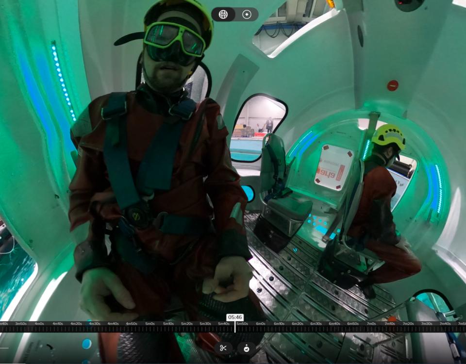 man i räddnignsdräkt inne i en vattenfylld helikoptersimulator