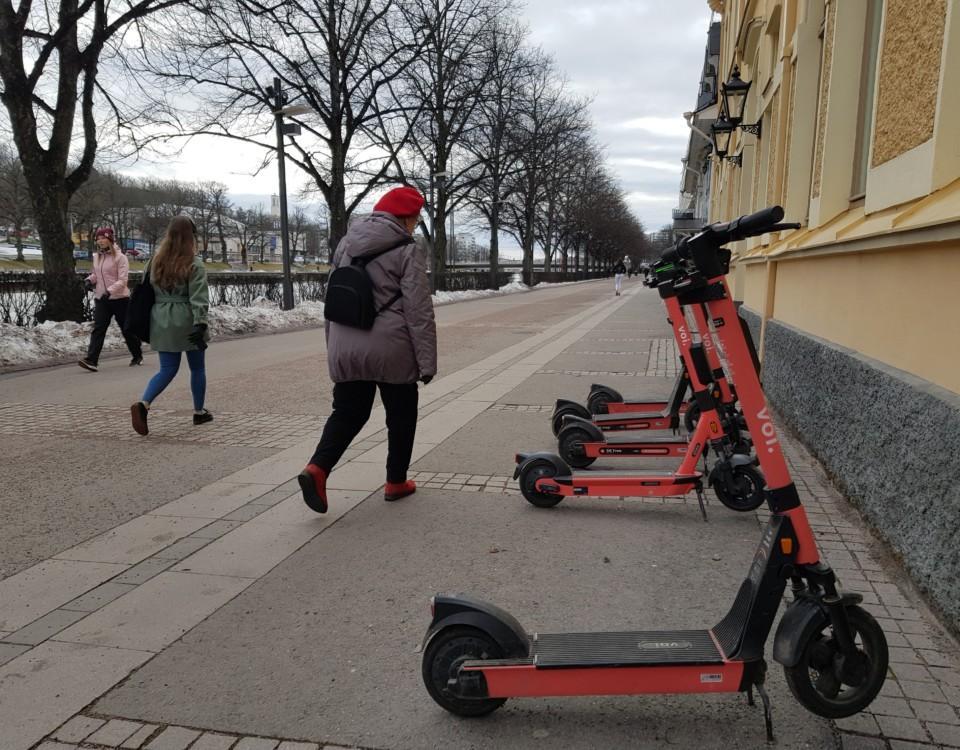 personer spatserar förbi elsparkcyklar vid åstrand