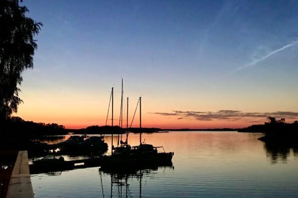 solnedgång över bryggor med båtar