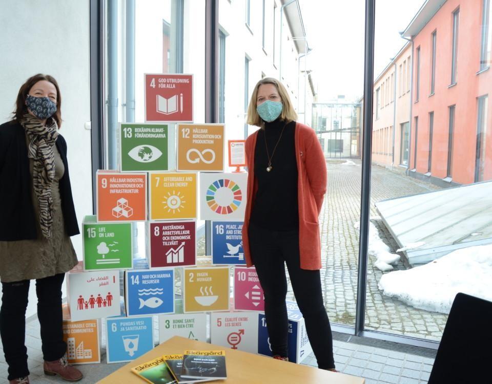 två kvinnor står framför stora pusselbitar som berättar om agenda 2030-mål, texter om en hållbar natur