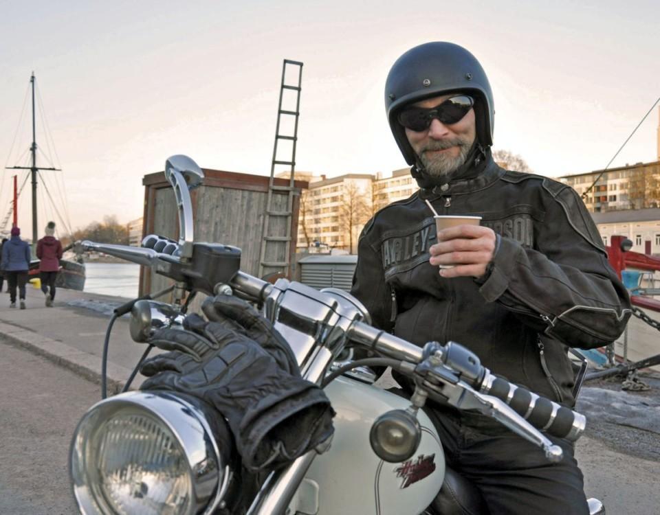 Man sitter på motorcykel och dricker kaffe