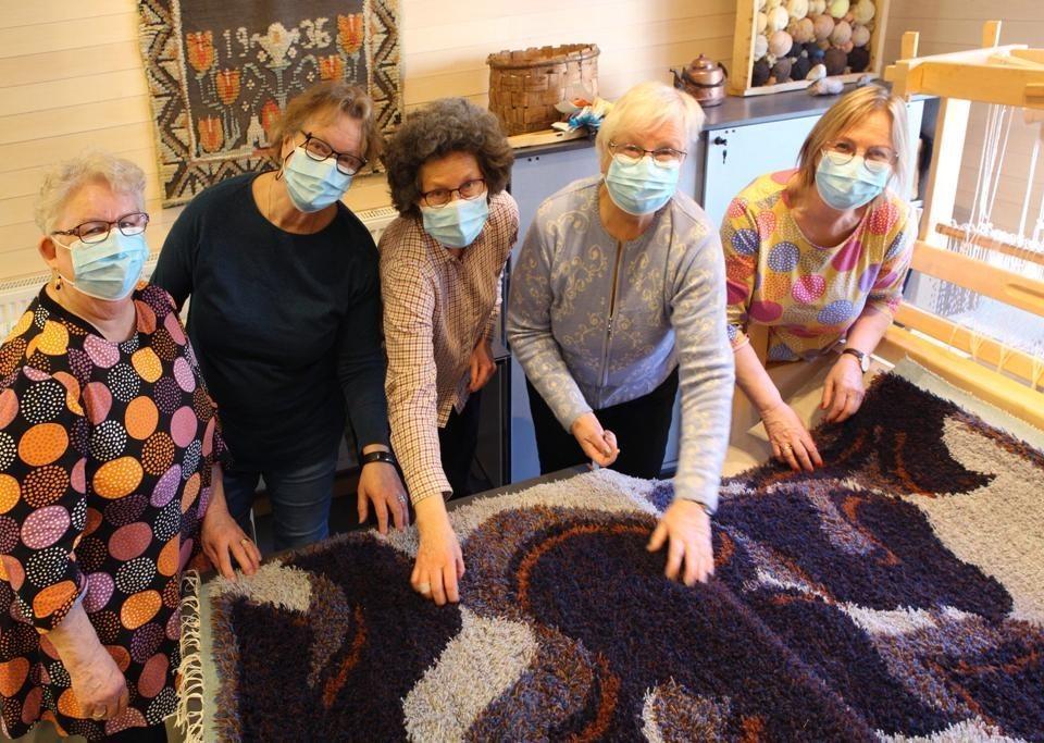 fem kvinnor samlade runt en rya som ligger på ett bord