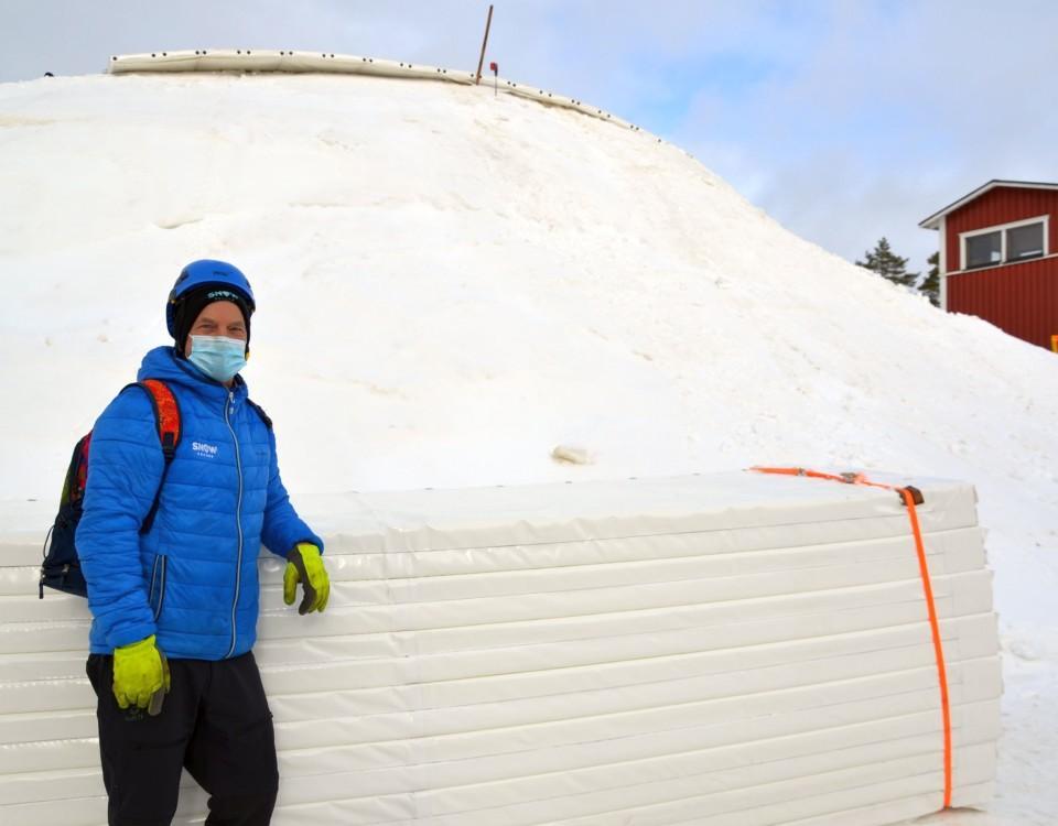 en man vid en hög av snö