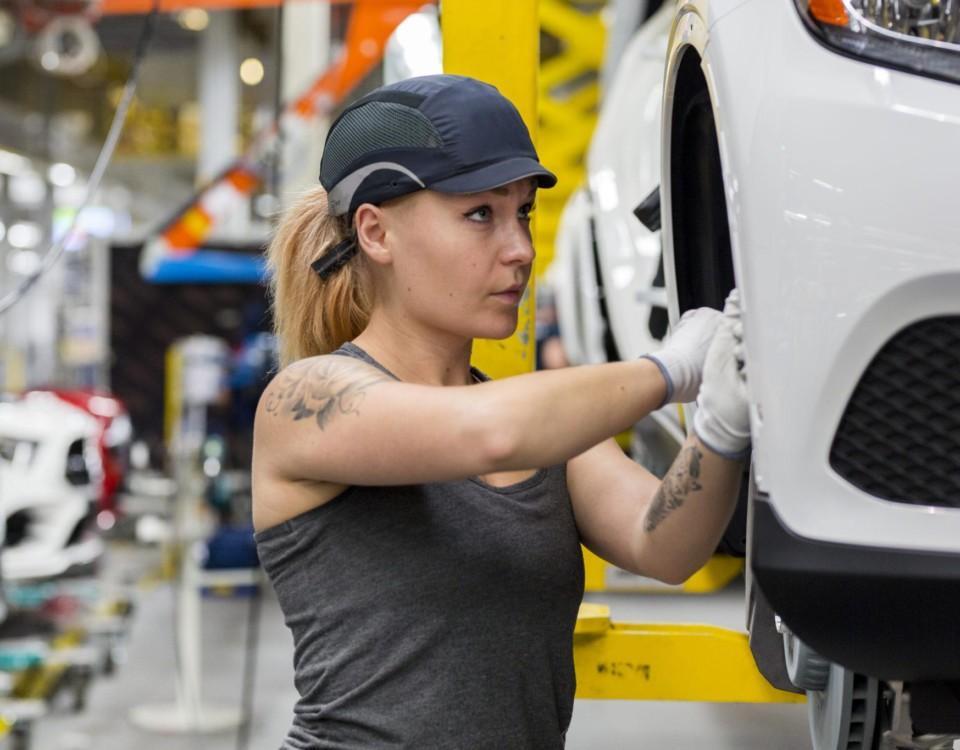 Kvinna som gör något på en bil i en fabrik.