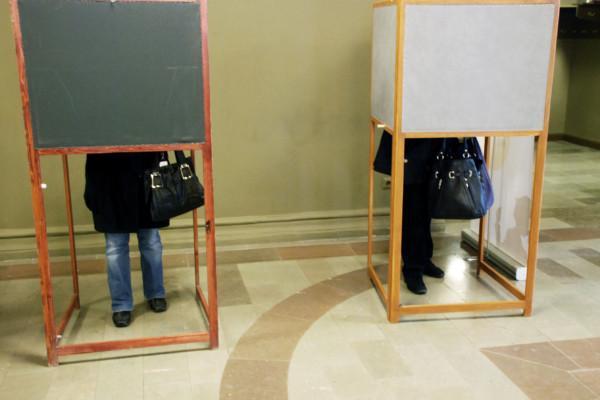 en vallokal och två väljare i bås