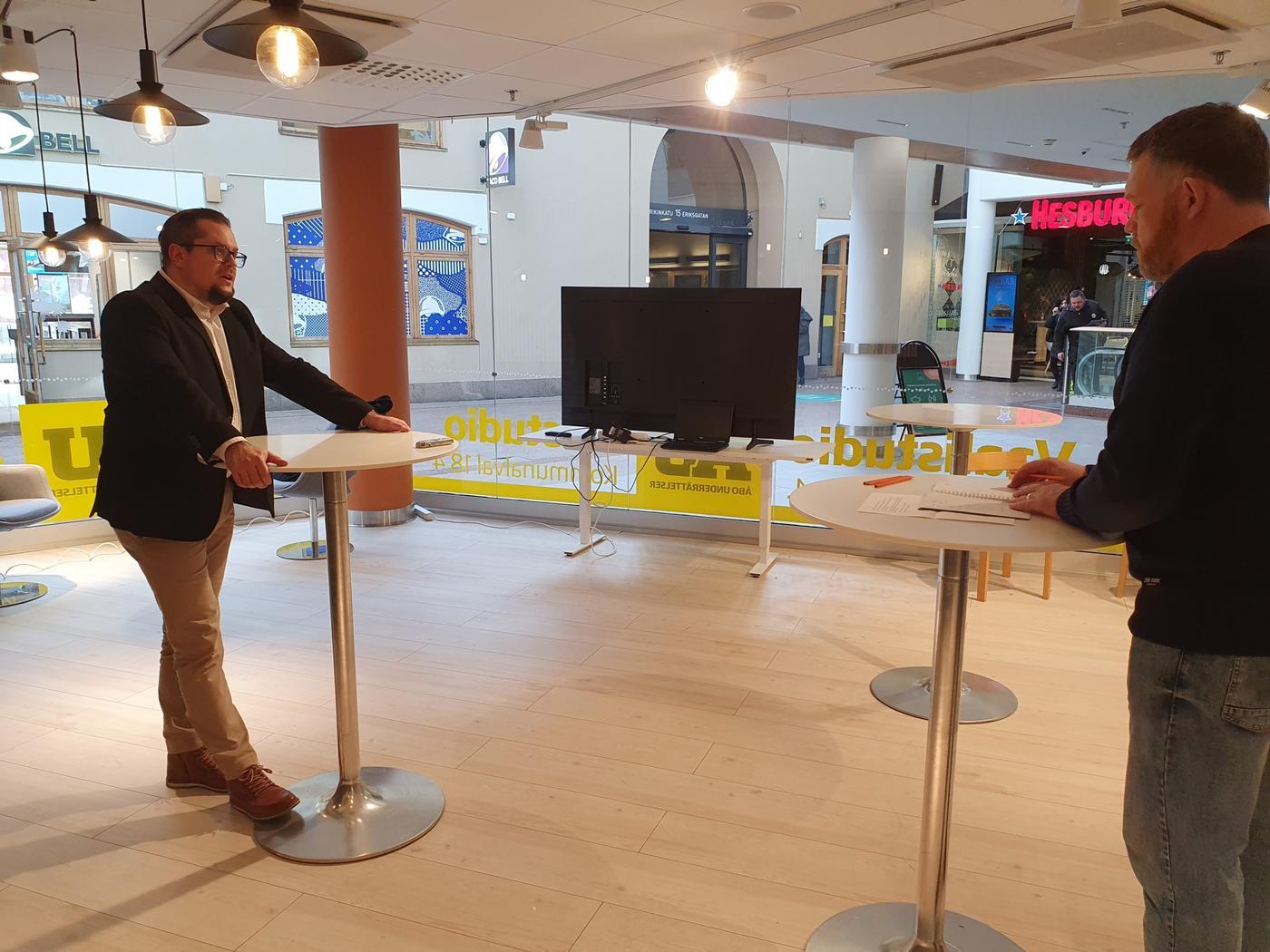 två män står och samtalar med ett par cafébord emellan sig