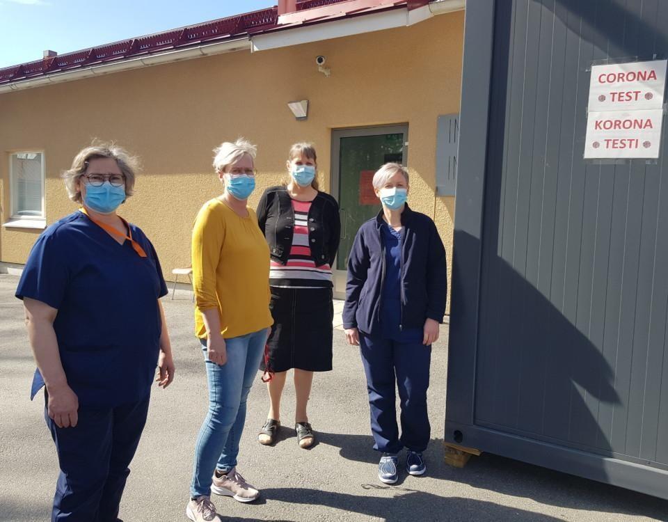 fyra damer med munskydd utanför en vårdcentral